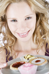 A portrait of a young woman holding a plate of assorted cakes