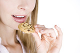A young blonde woman eating a cookie, close-up