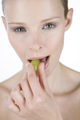 A portrait of a young woman eating a grape, close-up