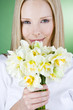 A portrait of a young blonde woman holding a bunch of daffodils