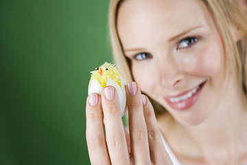A young woman holding an Easter chick toy