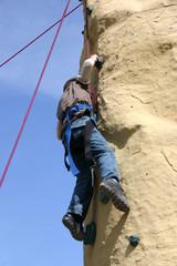 Junge klettert an Kletterwand