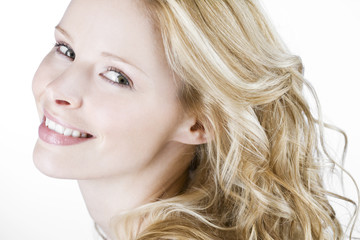 A young blonde woman smiling, side view