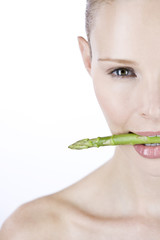 A young woman with asparagus in between her teeth, right side