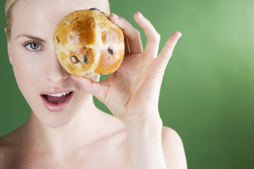 A young woman holding a hot cross bun in front of her eye