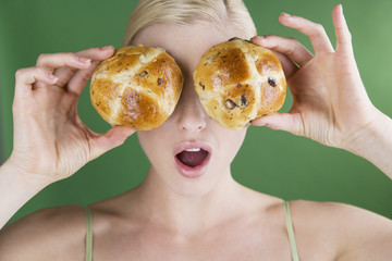A young woman holding two hot cross buns in front of her eyes