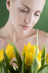 A young woman holding a bunch of yellow tulips looking down