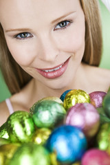 A young blonde woman holding a basket of Easter eggs, close-up