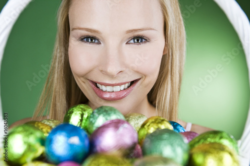 A young blonde woman holding a basket of Easter eggs, smiling
