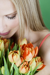 A young woman holding a bunch of orange tulips, looking down