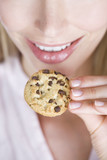 A young woman eating a cookie, close-up