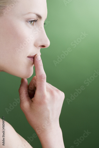 A young woman touching her upper lip, side view