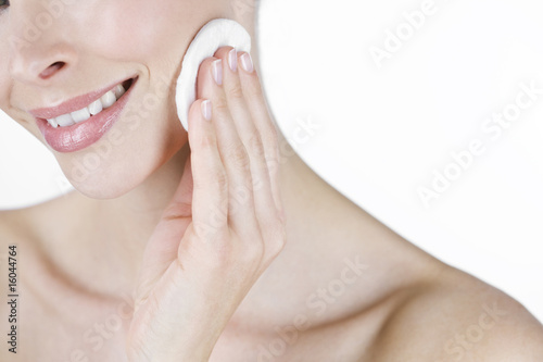 A portrait of a young woman cleansing her face