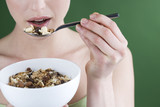 A woman eating a bowl of muesli, close-up