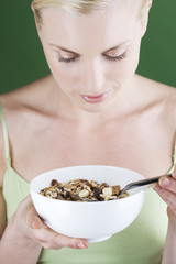 A young woman holding a bowl of muesli