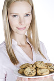 A young blonde woman holding a plate of cookies