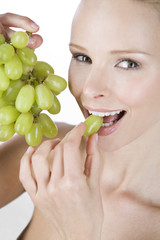 A portrait of a young woman eating grapes, close-up