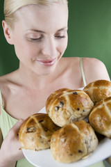 oung woman holding a plate of hot cross buns, smiling