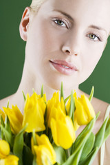 A young woman holding a bunch of yellow tulips, close-up