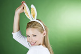 A young blonde woman wearing rabbit ears, smiling