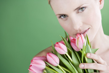A young woman holding a bunch of pink tulips