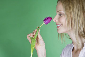 A young blonde woman holding a purple tulip, side view