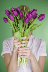 A young woman holding a bunch of tulips in front of her face