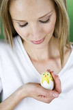 A woman looking at an Easter chick toy
