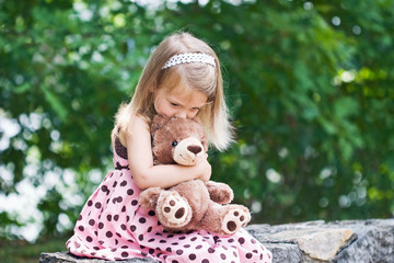 Adorable little girl giving her teddy bear a kiss on the head.