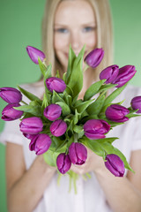 A young woman holding a bunch of purple tulips