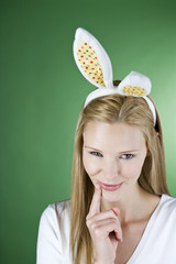 A young blonde woman wearing rabbit ears