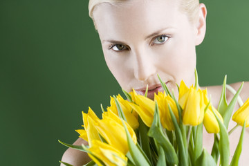 A young blonde woman holding a bunch of yellow tulips