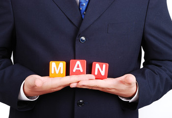 "Man in suit holding ""man"" letters"