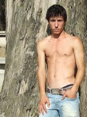 rapaz em tronco nú - encostado a uma árvore