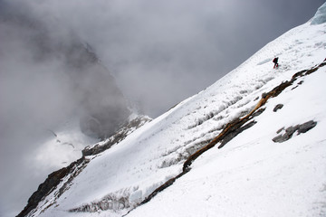 Climber traversing mountain slope at high altitude, Himalayas