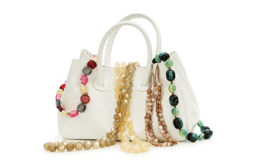 Woman bag and necklace isolated on white