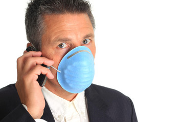 Businessman talking on the phone and wearing a flu mask