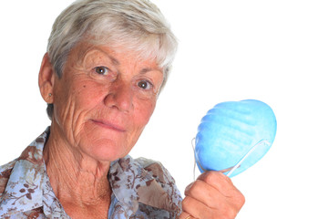 Elderly woman holding a flu mask.