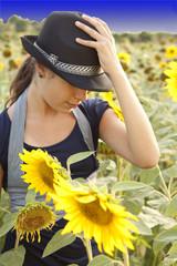Ragazza con cappello in un campo di girasoli
