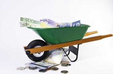 Green wheel barrel full of dollars bills
