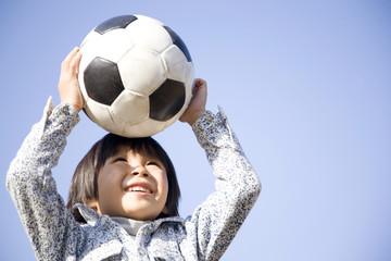 サッカーボールで遊ぶ小学生