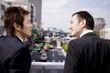 歩道橋で会話をするビジネスマン