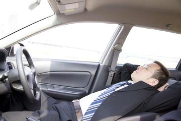 車内で仮眠をとるビジネスマン