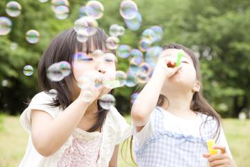 シャボン玉で遊ぶ2人の女の子