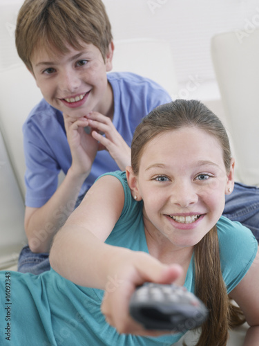 Young boy and girl with television remote