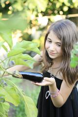 fillette qui ramasse des aubergines au jardin