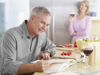 Couple in kitchen preparing meal with cook book