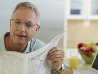 Man in kitchen reading newspaper