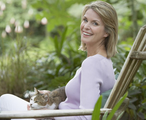 Woman outdoors in yard with cat on her lap
