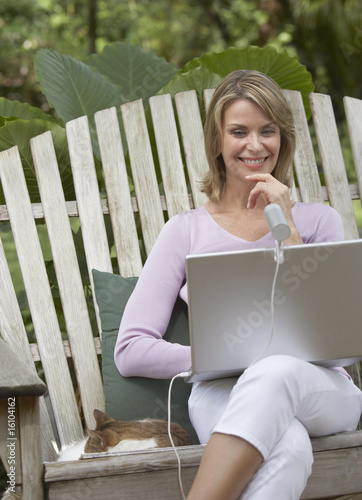 Woman outdoors in yard with cat and laptop